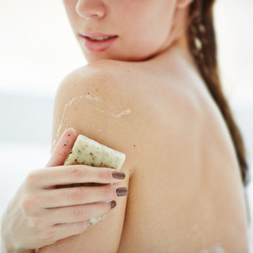 woman scrubbing skin on the back of her arm